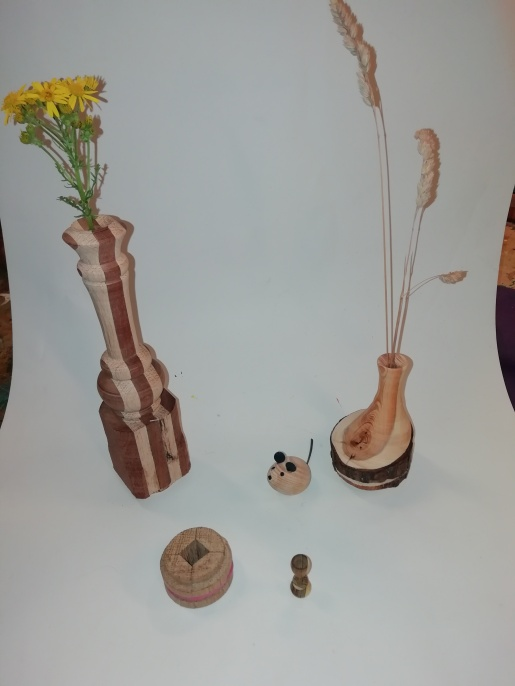 A yew vase turned off centre, the laminated vase both given to club members too complete. plus the mouse a miniature goblet & the home made jig Geoff used to hold the blank for the goblet.